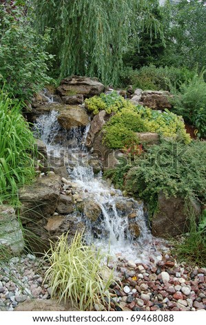 A man-made waterfall feature surrounded by lush foliage in a landscaped garden./Garden Water Feature