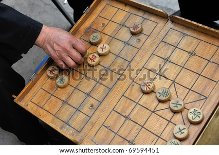 A man makes a move on a on a local Beijing Chinese chess game board. xiangqi, also known as Chinese chess, is an ancient board game played all over the world.