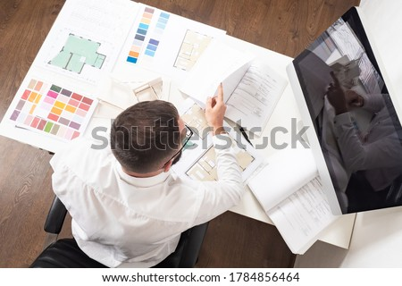 A man makes an estimate of construction work. Calculating the cost of a new home. Construction engineer at his Desk. Work on a construction project.
