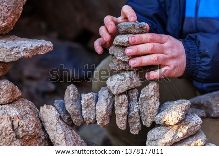 A man makes balancing stones in nature, perseverance hard work achievement of the goal, harmony of the inner world