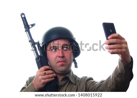 A man makes selfie in a military helmet with a rifle in his hands on a white background