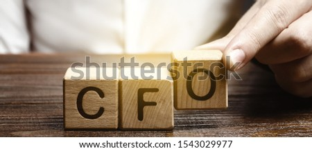 A man makes the word acronym abbreviation CFO. Chief Financial Officer. Financial management in business and company. Risk. Development and growth. Appointment to a new post, promotion.