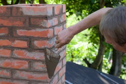A man making masonry works, working with a trowel and making a chimney of red bricks