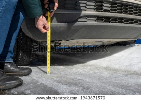 A man measures the ground clearance of a car with a tape measure . Evaluating a vehicle's off-road capabilities. Winter road. Imagine de stoc ©