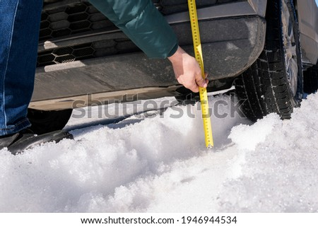 A man measures the ground clearance of a car with a tape measure . Evaluating a vehicle's off-road capabilities. Winter road. A snowy rut. Imagine de stoc ©