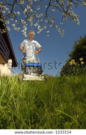 A man mowing long grass in spring, under a blossoming cherry tree, taken from a low viewpoint.