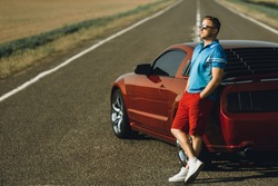A man near the red sportscar on a  background steppes