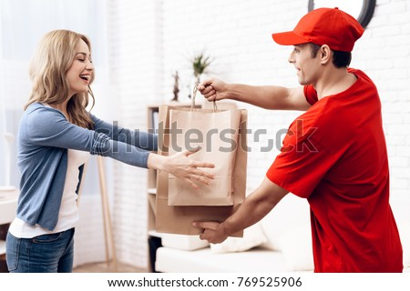 A man of Arab nationality works in delivery. The girl received the parcel delivery to the house. A man in red clothes brought a package to a young woman.