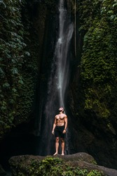 A man of athletic build at the waterfall. A man travels the world. Man at the waterfall. Travel to Bali Indonesia. A person travels through picturesque places. Lone traveler. Copy space
