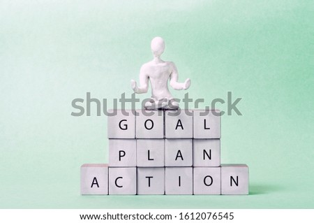"""a man of white plasticine sits in a lotus position on top of a cubed pyramid. inscriptions on cubes: """"goal, plan, action."""""""