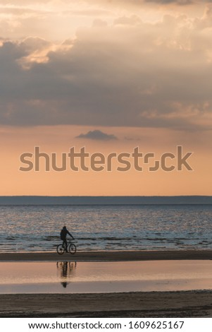 A man on a bicycle enjoys of calming scenic landscape above the sea. Gentle tones of the scenery. Bike ride along the Bay. Travel and vacation concept. Inspirational vertical photo. Beauty world.