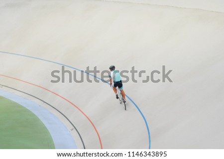 a man on a bicycle in a blue suit and helmet is riding the cycle track, the theme of sport and recreation  #1146343895