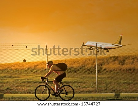 A man on a bicycle rides past as a plane lands at the airport