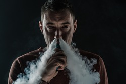 a man on a dark background smokes and blows smoke from his nose