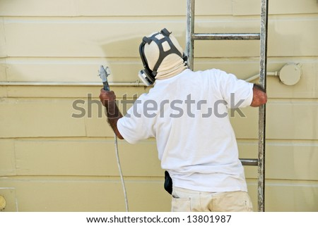 A Man On A Ladder Uses Spray Gun To Paint The Exterior Of A Wooden Building Stock Photo 13801987