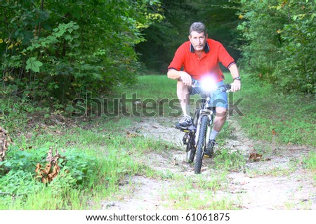 A man on a Mountain bike with a flashlight mounted on the handlebars coming through the woods with room for your text