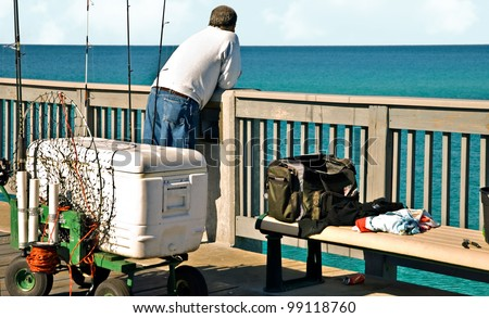 A man on a pier with fishing equipment around him.