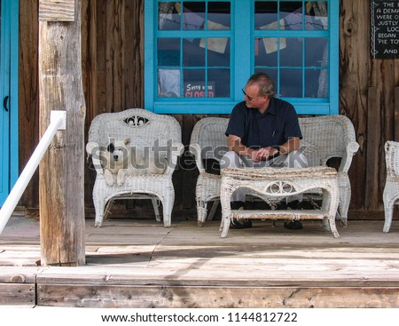 A man on a road trip in the western United States takes a break with a cute white dog dozing on the front porch of a country cafe.
