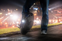A man on an electric mono wheel stopped while driving around the city. Night riding on an electric unicycle (EUC) with a bright headlight.