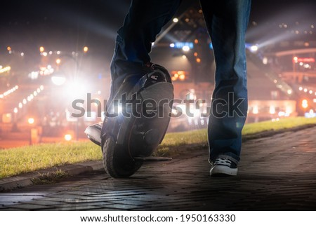 A man on an electric mono wheel stopped while driving around the city. Night riding on an electric unicycle (EUC) with a bright headlight. Stock photo ©