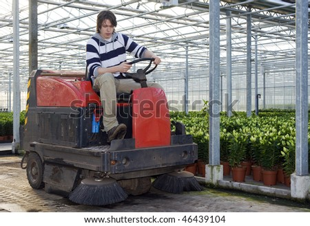 A man on an industrial cleaning machine cleaning the for Industrial concrete floor cleaning machines