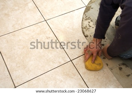 A man on his knees installing a ceramic tile floor
