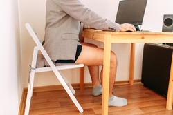 A man on home office while self-isolation and quarantine. A half dressed man in suit coat and panties.