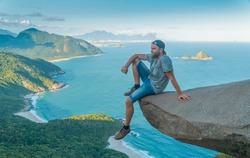 A man on the edge of the abyss. Pedra do Telegrafo is a tourist destination in Rio de Janeiro. Brazil.
