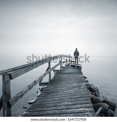 A man on the old broken wooden pier starring at the foggy Sea