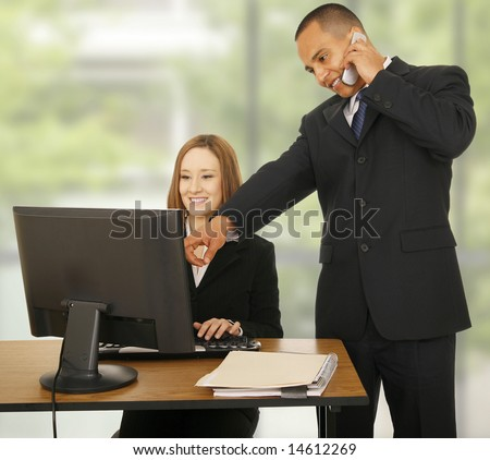 a man on the phone while pointing at computer screen while the other business woman looking at the screen and smiling. concept for business communication, or team work