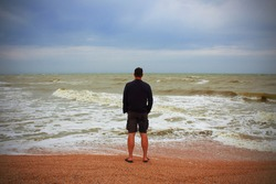 A man on the seashore looks into the distance. Selective focus. Background. Landscape.