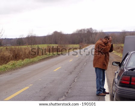 a man on the side of the road with his hands on head next to a broken down car