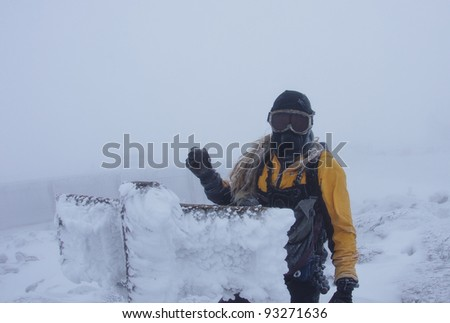 A man on the summit of Mount Washington in near whiteout conditions with face mask and goggles and rime ice