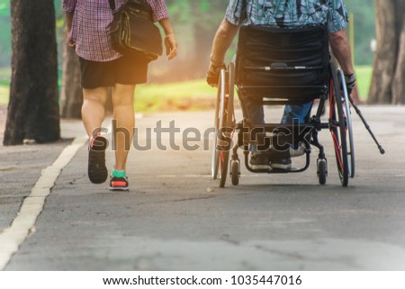 A man on wheelchair and his wife enjoying in the park,copy space.