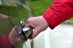 A man opens the door of a passenger car