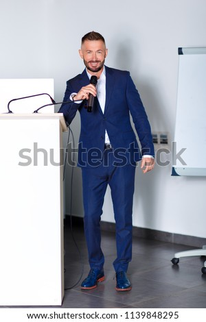 A man orator stands for the podium.Businessman in a suit behind the podium