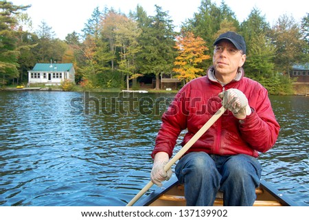 A man paddles a canoe on a lake in Vermont during fall foliage season. Summer cabins line the shore in the background.