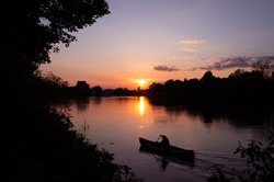 A man paddling alone in a boat along the Thames in the orange sunset.