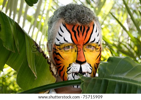 A man painted as a tiger, half hidden behind tropical leaves.