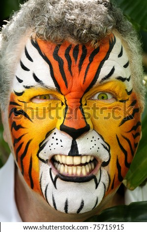 A man painted like a tiger making an angry expression.