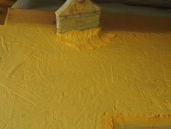 a man paints yellow paint with a brush