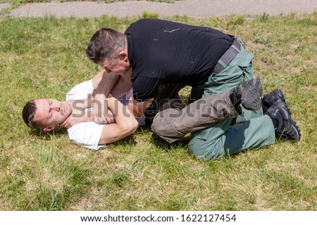 A man performs a reception to relieve strangulation while lying down.  Close up. Martial arts instructors demonstrate self-defense techniques of Krav Maga