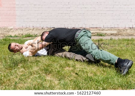A man performs a reception to relieve strangulation while lying down. Martial arts instructors demonstrate self-defense techniques of Krav Maga