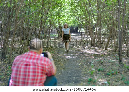 A man photographs a girl walking through the forest.