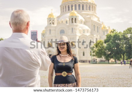 A man photographs a woman against the background of the Orthodox Church
