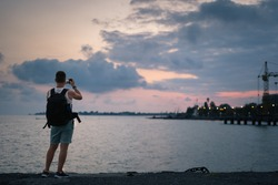 A man photographs the sea and sunset. A man with a backpack on the beach takes photos of the sea at sunset on a smartphone