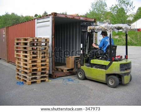 A man picking up pallet with truck
