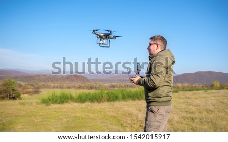 A man pilots a drone in nature by controlling it from a remote control.