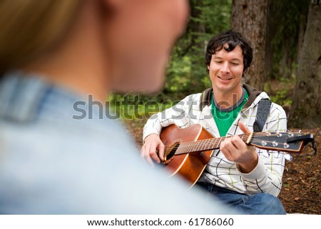 A man playing a guitar and singing for a woman