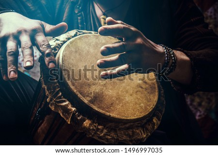 A man playing an ethnic percussion musical instrument jembe. Drummer playing african music #1496997035